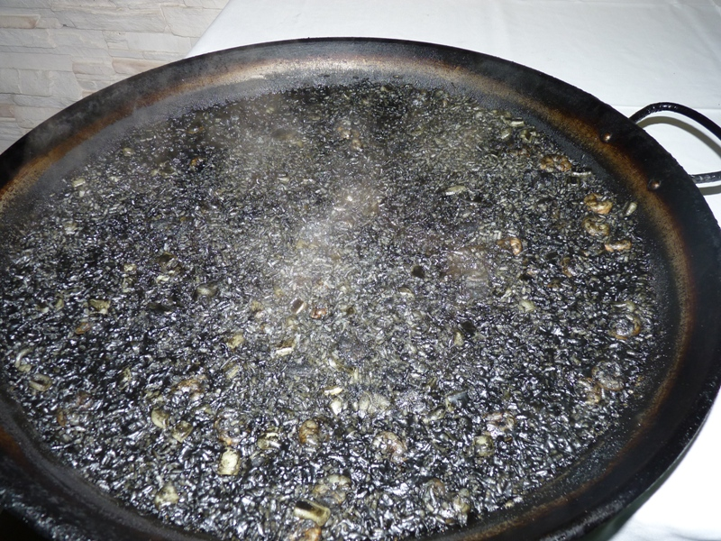 Arroz Negro steaming in a paella