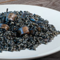 Black rice paella recipe Arroz Negro and lemon in a plate